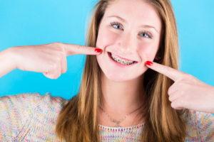 снимают брекеты с зубов